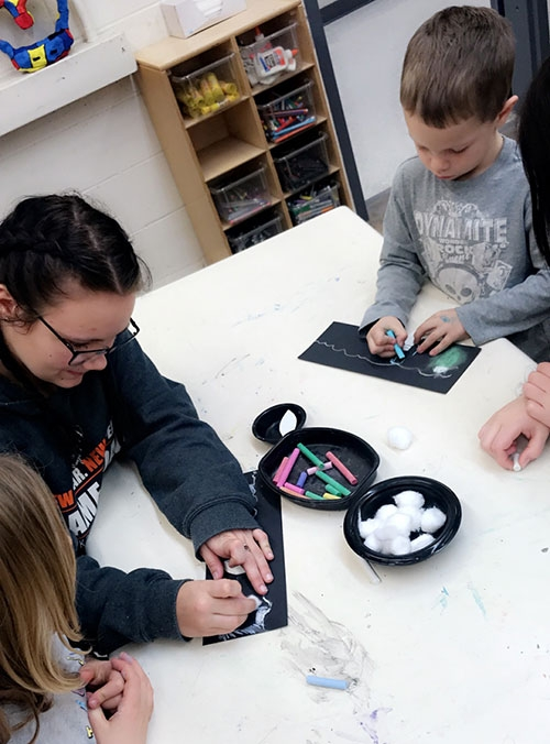 Older And Younger Students Collaborate On Art Projects And Fun For