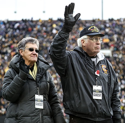 """John and Eileen Curtin of rural Waukon wave to the fans at Kinnick Stadium in Iowa City as John was honored as a """"Hawkeye Hero"""" on the..."""